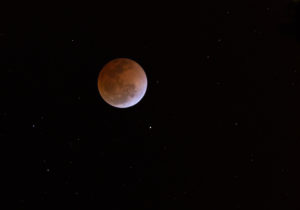 This is a photograph of the Lunar Eclipse Blood Moon moving out of its maximum stage at 3:00am Central Time. Background star field added from same sky location later.
